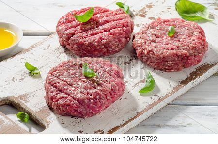 Raw Ground Beef Burger Steak Patties On A White Wooden Cutting Board.