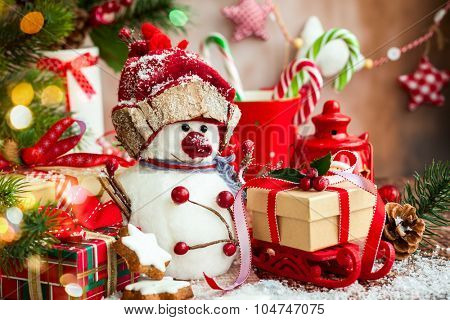 Snowman, Christmas presents and sweets  over wooden background