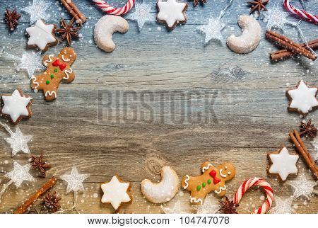 Christmas decoration with gingerbread cookies,christmas lights and spices on the old wooden board