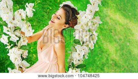 Young beautiful nymph on a swing made of flowers