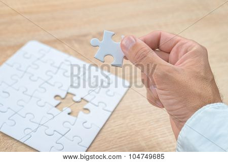 Businessman Hand Putting A Missing Piece Into Jigsaw Puzzle