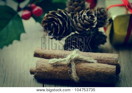 Cinnamon Sticks Bundle, Holly And Fir Cones On Oak Planked Table - Retro Hues