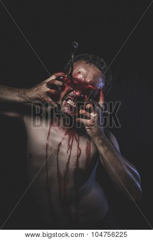 Halloween, naked man with blindfold soaked in blood