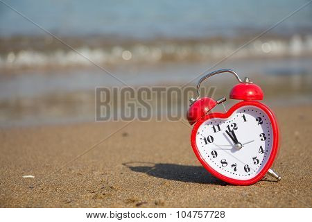 Red Clock In Shape Of Heart On A Sandy Beach Background.