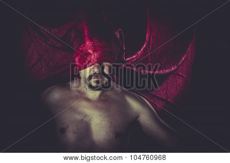 Hell, naked man on large red cloth over his eyes