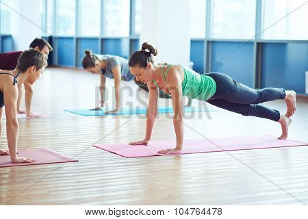 Group of young people doing yoga exercise in gym