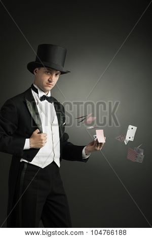 magician holding playing cards, showing focus, juggles