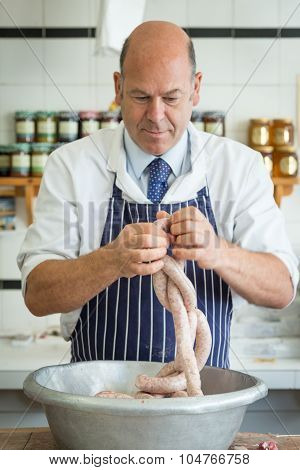 Male Butcher Linking Sausages