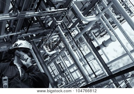 refinery worker with giant pipelines construction, selenium toning.