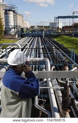 oil worker pointing out over long pipelines constructions leading to fuel tanks