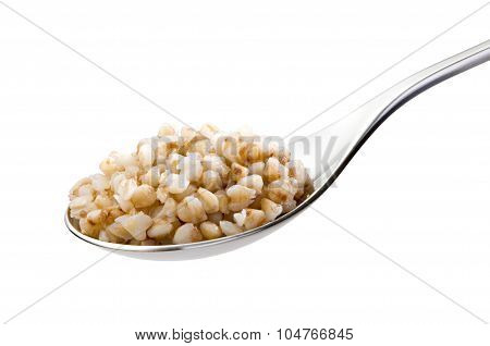spoon with boiled buckwheat close-up isolated on white