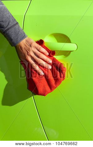 Hand with cloth washing a car. Waxing and polishing.