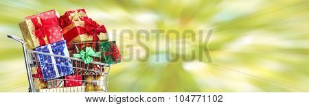 Shopping cart with Xmas gifts over green banner background.