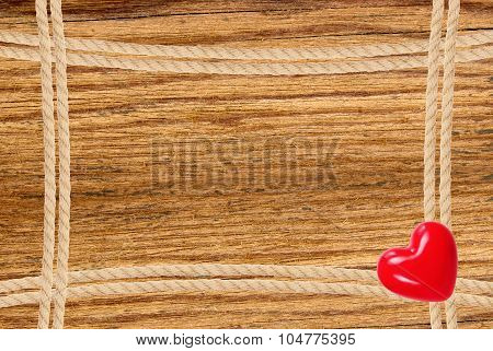 Frame Composed Of Rope And Red Heart Over Wooden Background