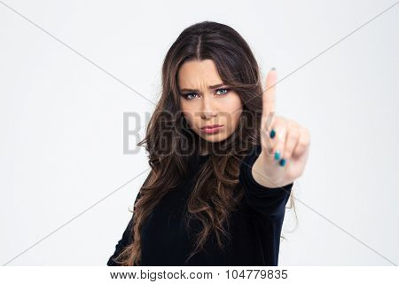 Portrait of a young girl showing disagree sign with finger isolated on a white background