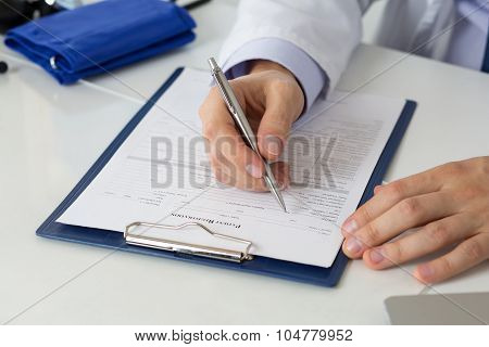 Close Up Of Doctor's Hands Writing Prescription