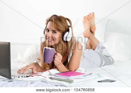 Young Beautiful Smiling Woman Laying On Her Bed With Laptop