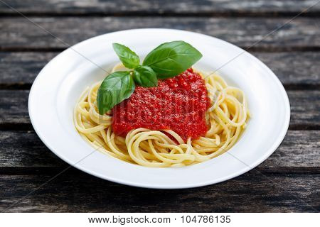 Spaghetti With Marinara Sauce And Basil Leaves On Top, On Wooden Table.