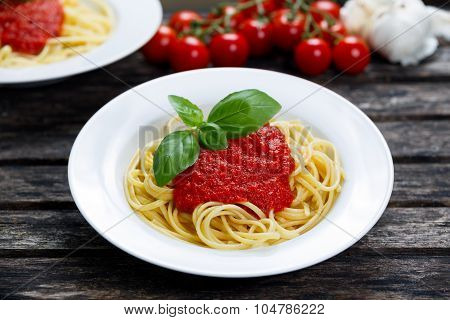 Spaghetti With Marinara Sauce And Basil Leaves On Top, Decorated With Vegetables. On Wooden Table.