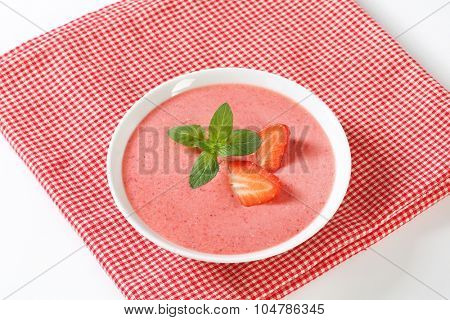 bowl of strawberry soup on checkered place mat