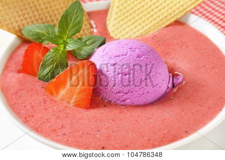 detail of strawberry soup with scoop of blueberry ice cream and crispy wafers