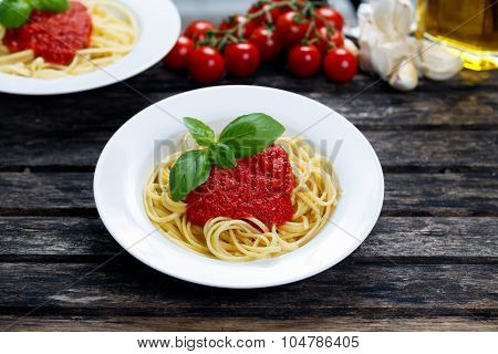 Spaghetti With Marinara Sauce And Basil Leaves On Top, Decorated With Vegetables, Olive Oil. On Wood