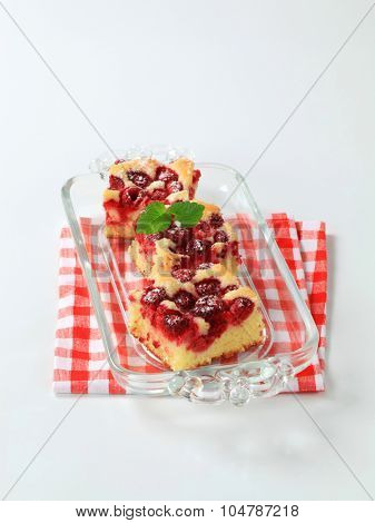 raspberry sponge cake squares on glass tray