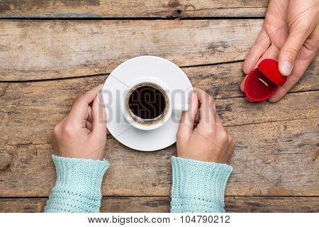 Woman Holds Cup Of Coffee And Man Gives Gold Ring As A Gift