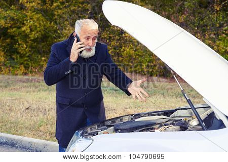 discontented senior man talking on the phone and looking under the hood of breakdown car