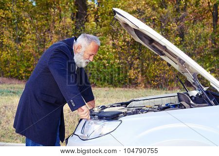 senior man looking under the hood of breakdown car at outdoor