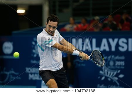KUALA LUMPUR, MALAYSIA - OCTOBER 02, 2015: Kazakhstan's Mikhail Kukushkin hits a backhand return in his match at the Malaysian Open 2015 tennis tournament held at the Putra Stadium, Malaysia.