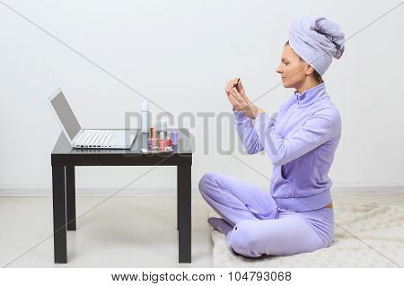 Young pretty woman in blue bath towel on head with nail varnish over mirror table