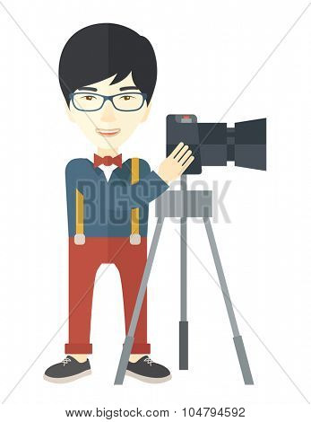 An Asian photographer in glasses standing with camera on a tripod vector flat design illustration isolated on white background. Vertical layout.