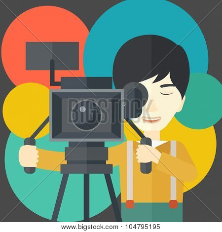 An Asian cameraman looking through movie camera on a tripod vector flat design illustration. Square layout.
