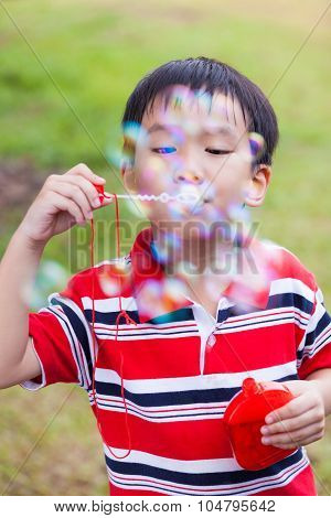 Asian Child Blowing Soap Bubbles In Summer Park, Nature Background