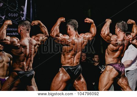 men bodybuilder straining muscles in back and hands