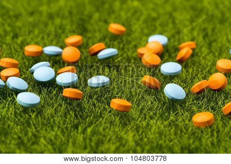 Scattered orange and blue round pills on the green grass