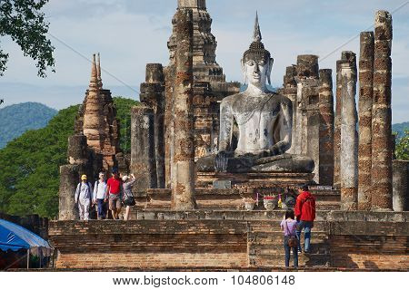 People visit Buddha statue at Wat Mahathat in Sukhothai, Historical park Sukhothai Thailand.