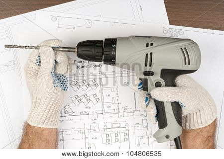 Mans hands in gloves holding drill