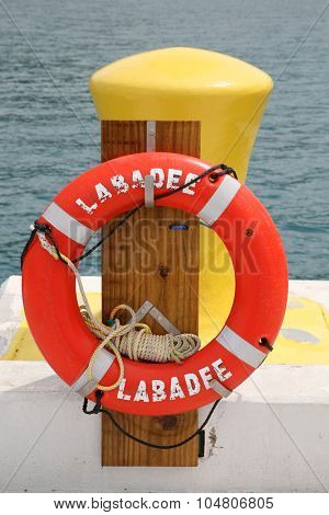 LABADEE, HAITI - SEPTEMBER 27, 2015:  Labadee, Haiti Photo Op on the Dock with an orange Life Ring next to a Hitching Post for Cruise Ships and Boats to tie to the dock.