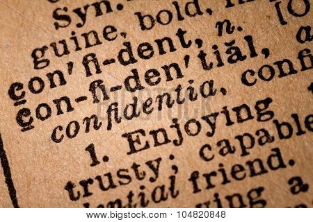Close-up Of An Opened Dictionary Showing The Word Confidential
