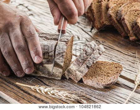 Man's hands cutting rye-bread on the wooden plank.