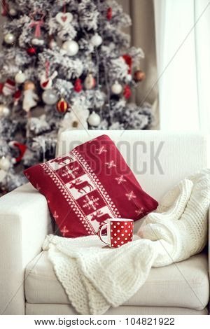 Opened book and a cup of tee on the cozy chair with warm blanket and cushion on it near Christmas tree