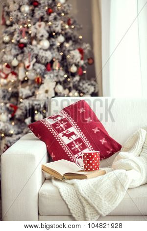 Opened book and a cup of tee on the cozy armchair with warm blanket and cushion on it near Christmas tree. Text in the book is not recognizable.