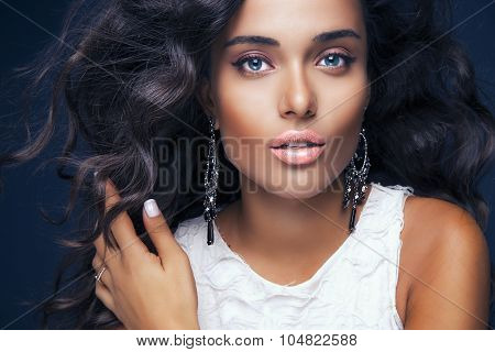Beautiful model with elegant hairstyle and glamorous jewelry .