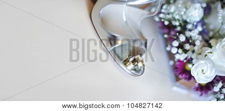 wedding concept with white roses and silver shoes