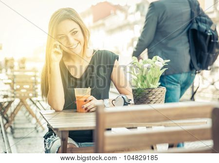 Woman Talking On The Phone While Sitting In A Bar