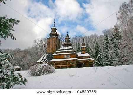 Old Church Slavonic Orthodox Church In The Snow, With Three Crosses On The Domes. Covered With Woode