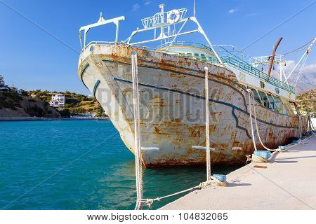 Old rusty abandoned ship in port of Aghia Galini, Crete island, Greece