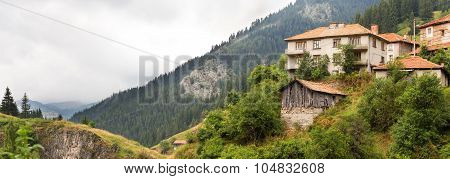 Village houses and outbuildings in the village of Mugla in coniferous forest on the steep slopes of the Rhodope Mountains in cloudy weather (Rhodopes Bulgaria)